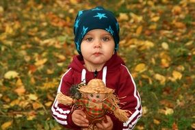 child with a doll in hands on the background of autumn leaves in the park