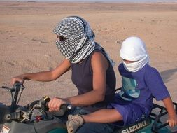 mother and baby ride a desert quad bike