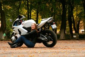 girl in a leather jacket sitting on a background of motorcycle