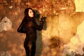 Girl with black hair wearing a leather jacket against the background of the wall