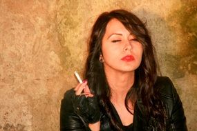 girl in a leather jacket with a cigarette in his hand covering her eyes