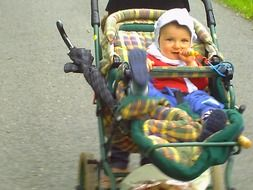 cute baby girl in a baby carriage with pacifier