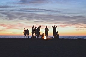 group of friends on the beach rest at night