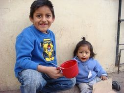 brother and sister are eating on the street in Peru
