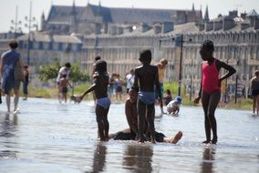 dark skin childreen playing in water on street