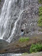 young man posing at waterfall, france, cascade du ray pic