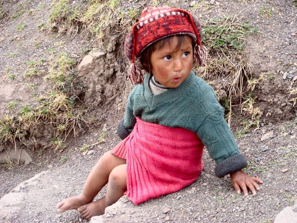 Peruvian little girl is sitting on a stone
