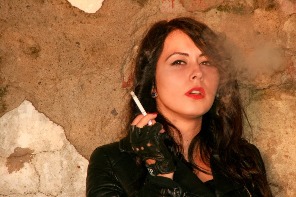 dark-haired girl in a leather jacket with a cigarette in her hand