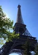 View from below of the Eiffel Tower in the glare of the sun