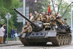 Soldiers with a red flag on a tank at the military-historical parade in Prague