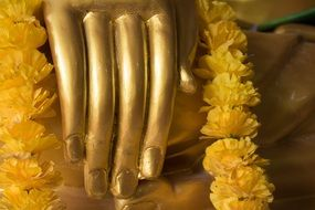 golden buddha statue with yellow flowers