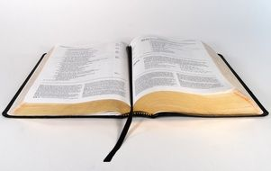 An open bible on a white surface