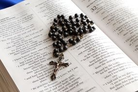 rosary cross on the Bible book