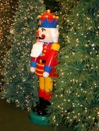 nutcracker, colorful figure at christmas trees