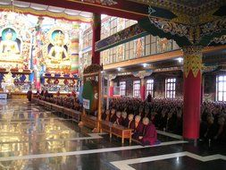 Tibetan monks are sitting on the floor of the monastery