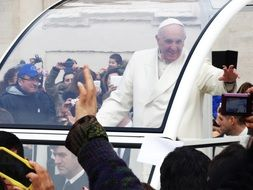Pope francis among people in a special car