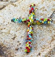 colored bead cross on a rock