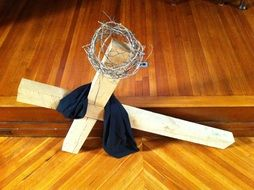 photo of a wooden cross of black fabric and a metal wreath