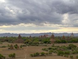 bagan temples in picturesque landscape under cloudy sky, burma