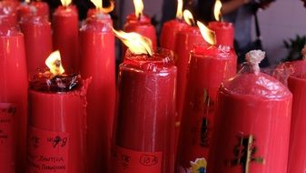 burning red candles with chinese symbols