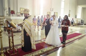 orthodox wedding, pastor, bride and groom in church, russia