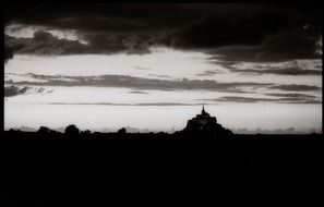 Monastery on mont st michel in the dark against a background of clouds