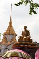 golden statue of a monk on a hill