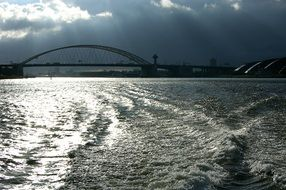 bridge across rhine river beneath stormy clouds, netherlands