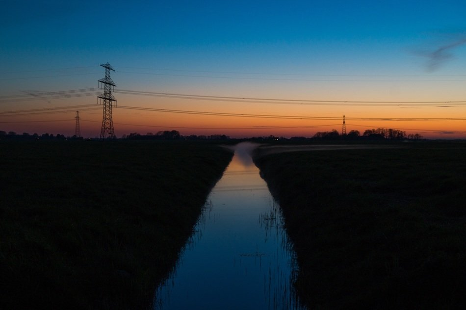 electrical wires over a stream at dusk