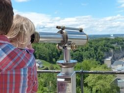 the child is looking through a telescope