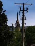 steeple among power piles and tree tops