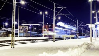 train passing by station at snowy winter night