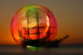 view of sailing ship on sea at sunset through soap bubble