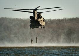 military helicopter with soldiers over the water