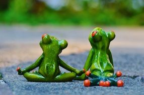 two ceramic frog figures hold hands and look up