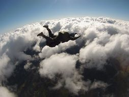 skydiver over clouds