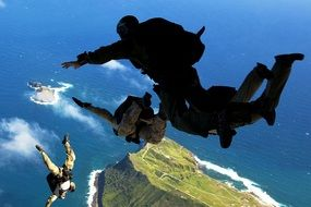 Paratroopers soar in the air above the ocean
