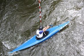 athlete in blue canoe floats on water