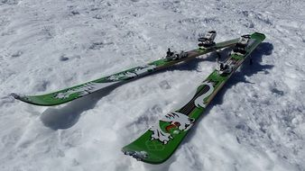 green tourist skis in the snow