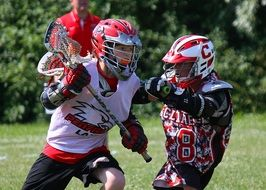 two male lacrosse players in game
