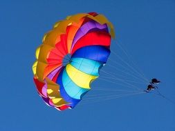 parasailing together on a multi-colored parachute