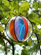 colorful children's ball on a green tree closeup