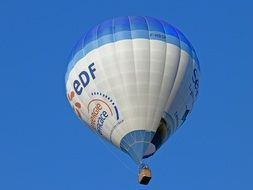 flying hot air balloon against a clear blue sky