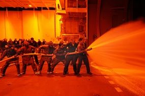 firefighters hold fire hose