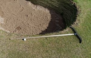 sand, rake and ball on a golf course