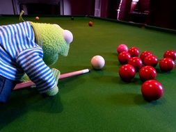 green frog playing billiards