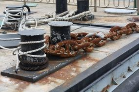 rusty chains on stakes in the port