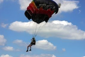 Jump with a parachute on a cloudy sky background