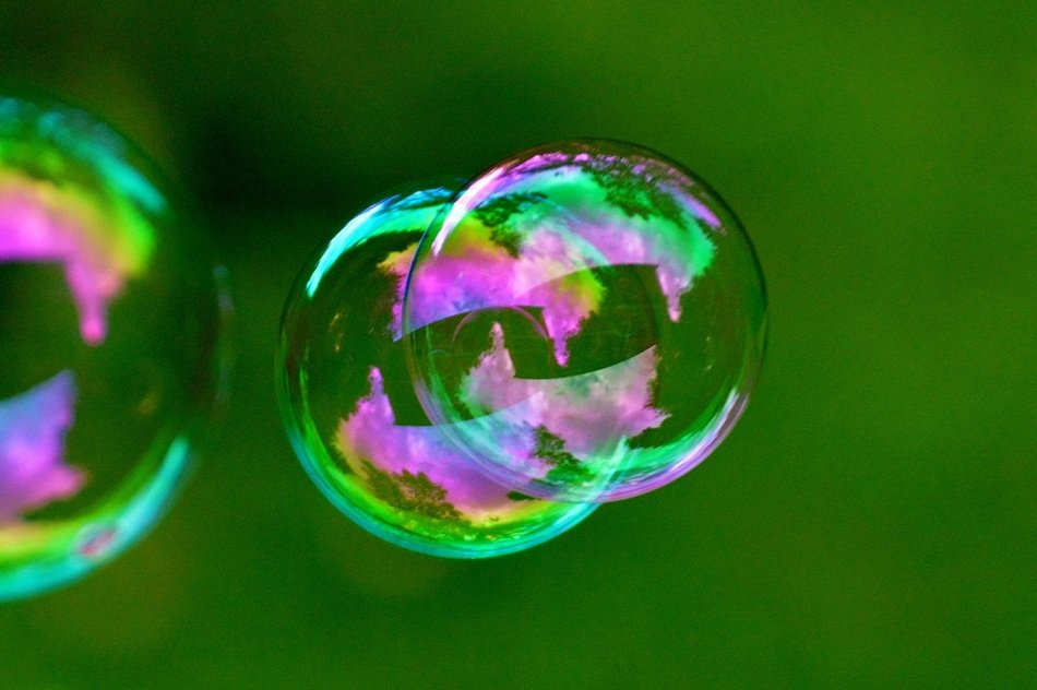 multicolored soap bubbles on a green background