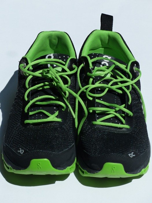 black sneakers with green laces